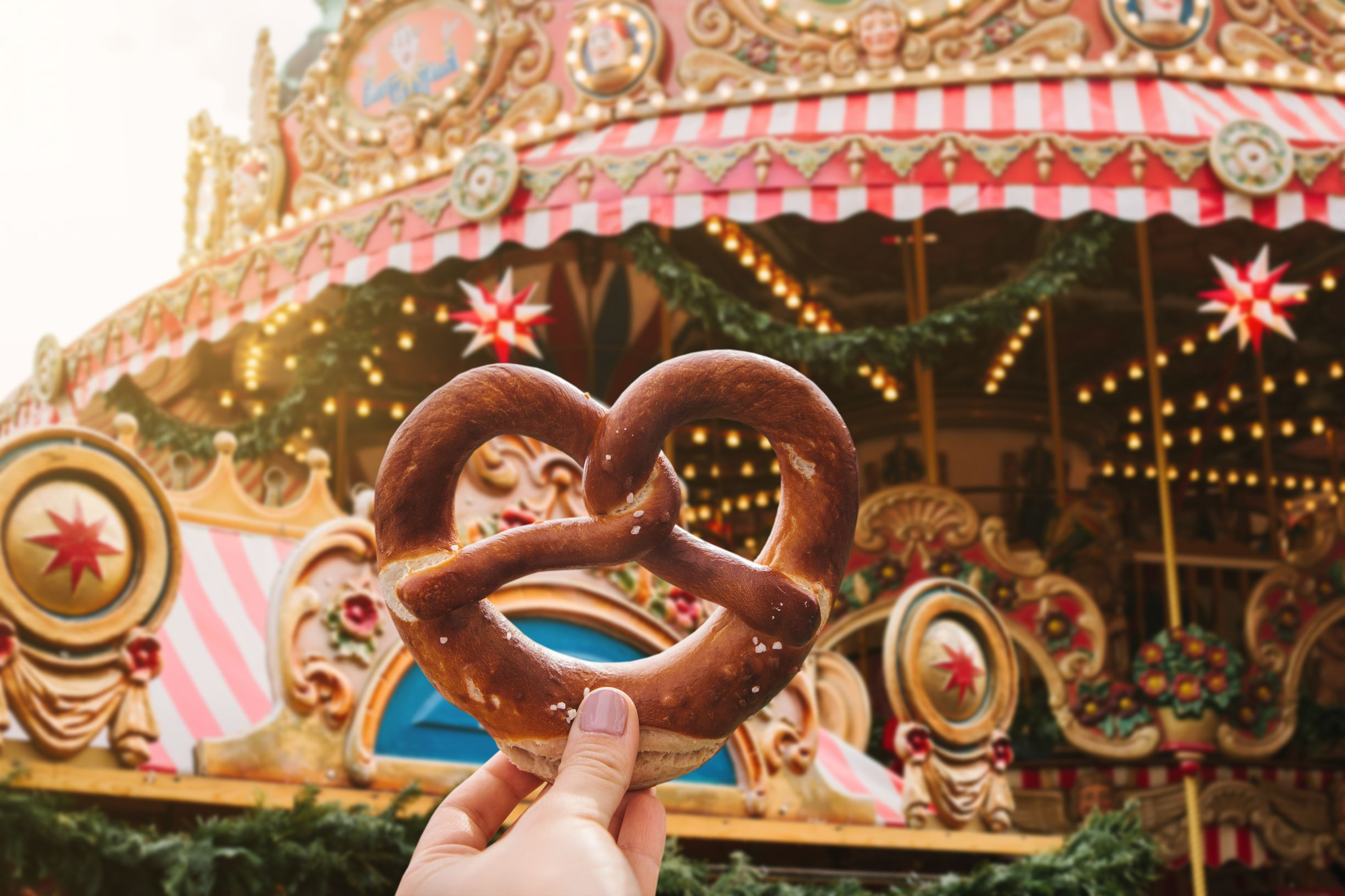 Photo of a large Bavarian pretzel with a Christmas Carousel in the background.