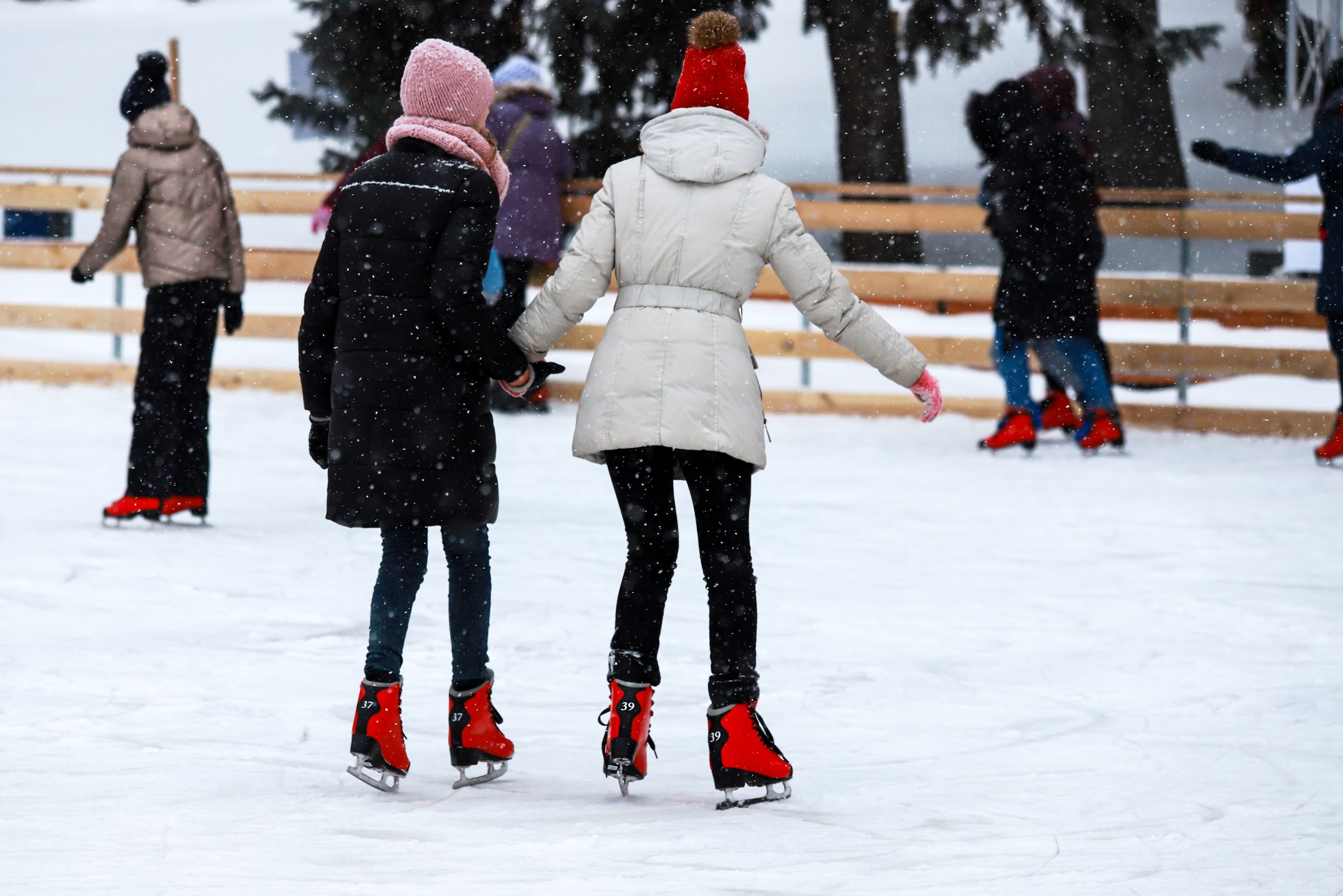 Photo of people skating on an outdoor ice rink.