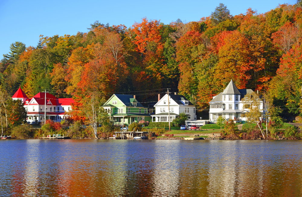 big houses along lake surrounded by colorful leaves of fall trees