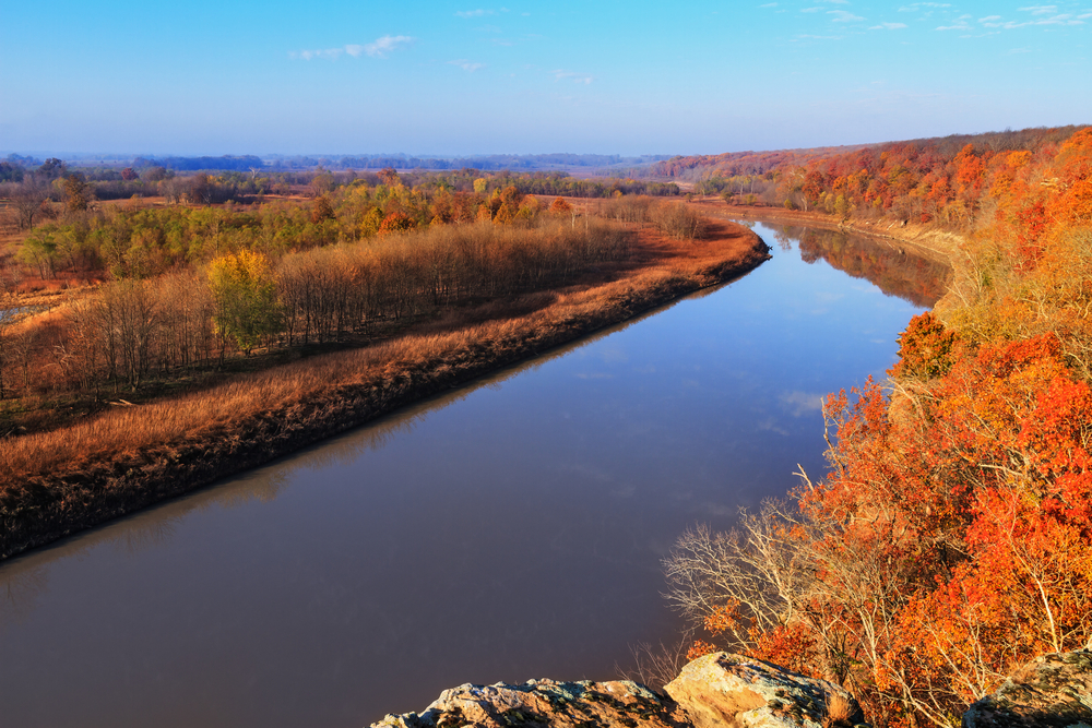 wide river lined with orange and red trees fall in the USA