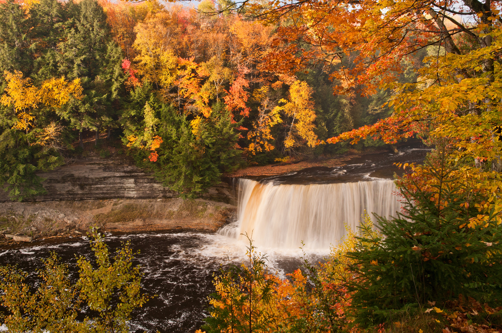 wide waterfall surrounded by fall colors fall in the USA