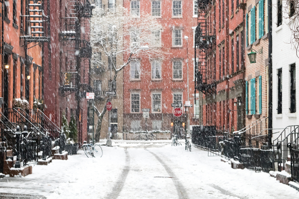 red brick buildings surrounding snowy side streets of New York in winter