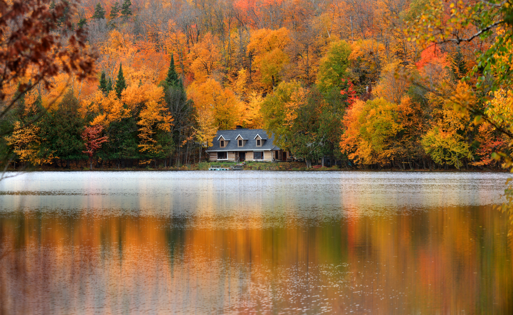 the beautiful reflections of the leaves in Lake Ouimet make it a stunning place to see fall in canada