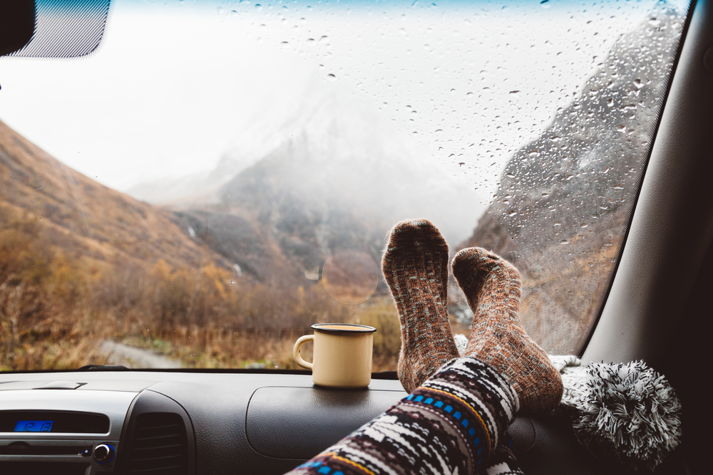 A passenger puts her socks up on the dashboard while it rains
