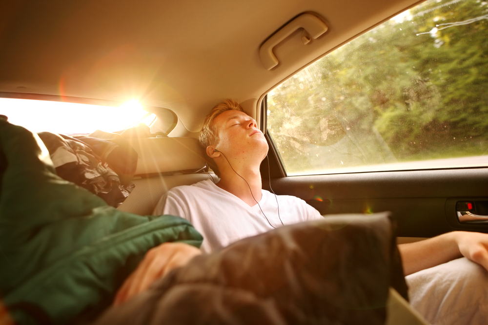A passenger sleeps in the car