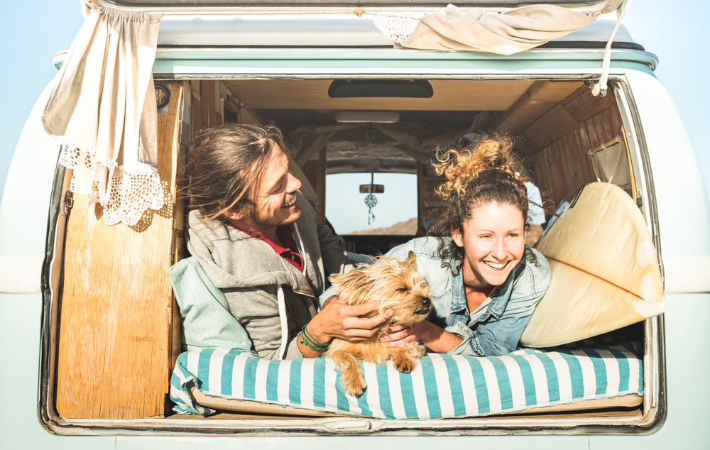 A couple and dog chill in the back of their van
