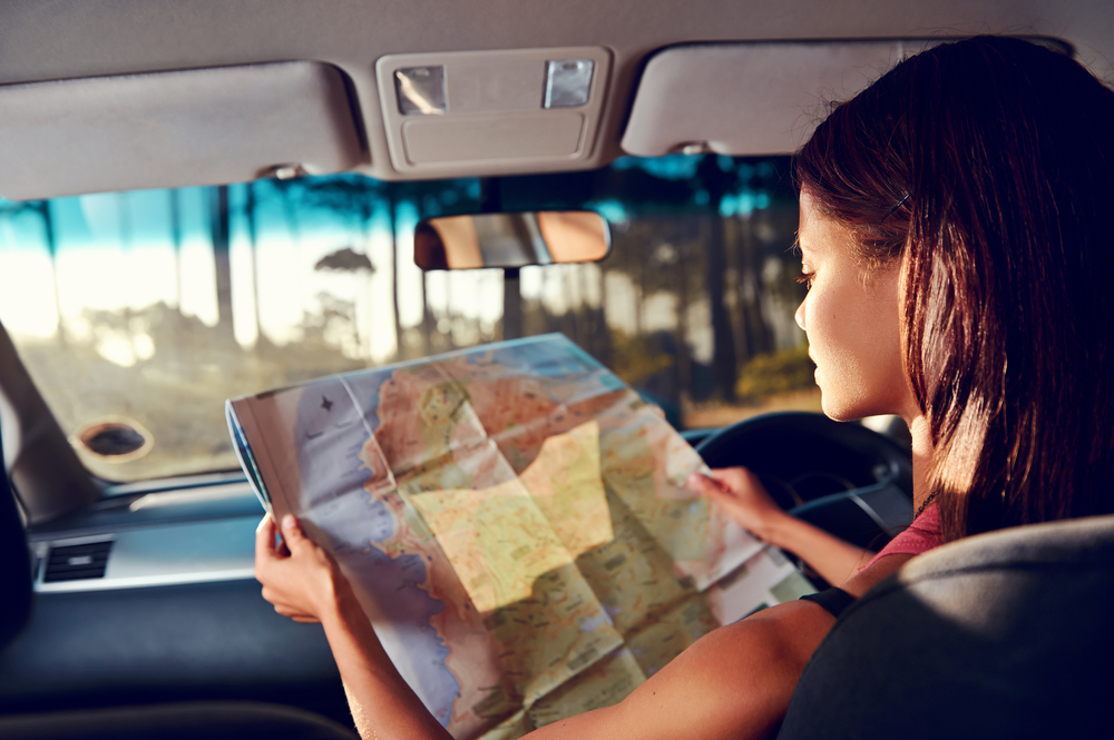 A girl looks at a map on a drive