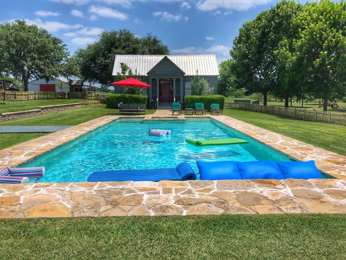 Photo of the exterior of a farmhouse Airbnb that has a pool.