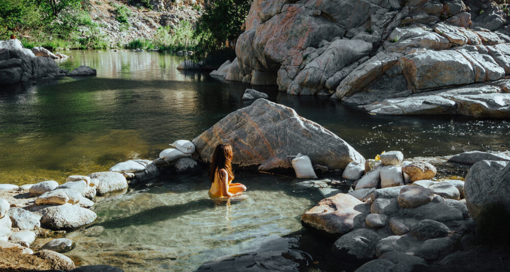 woman sitting in one of the best hot springs in california