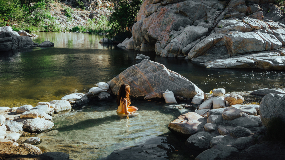 One of the best natural hot springs in California, Deep Creek Hot Springs, with a woman sitting in the middle of the warm water