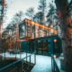 cabin made of three shipping containers stacked on each other in woods in winter