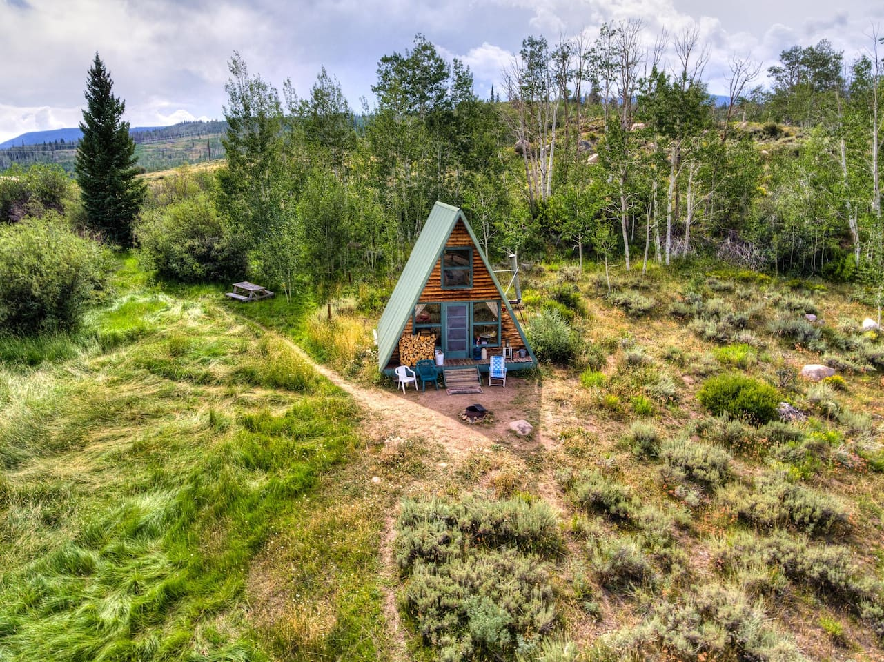wooden a-frame surrounded by greenery filled landscape cabins in the USA