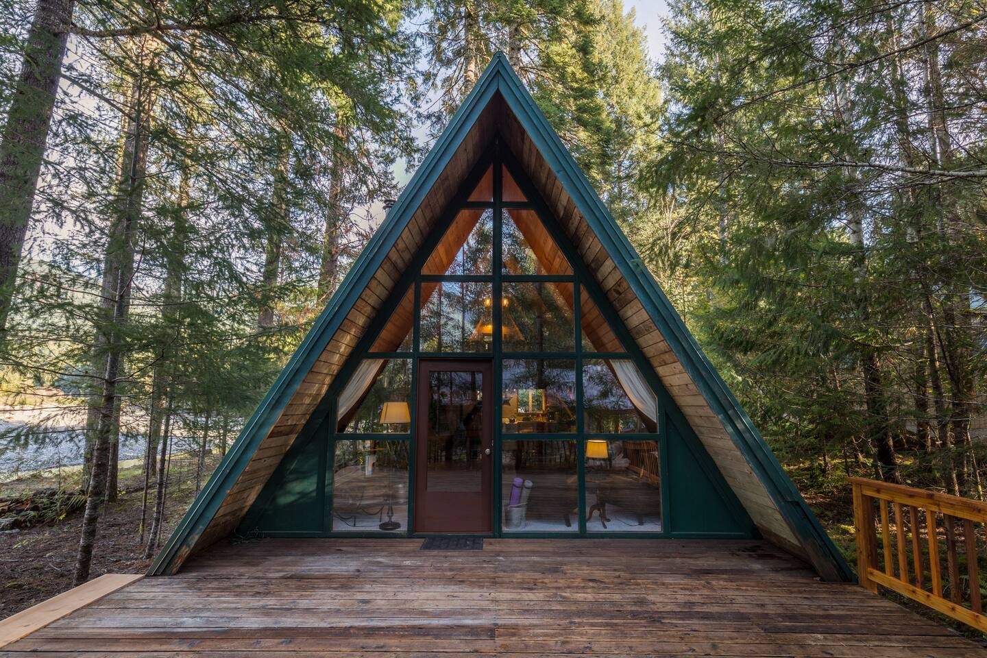 wide A-frame wooden cabin with green border and glass windows surrounded by trees