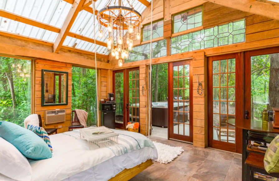 glass and wood interior with plush bed and boho chandelier cabins in the USA
