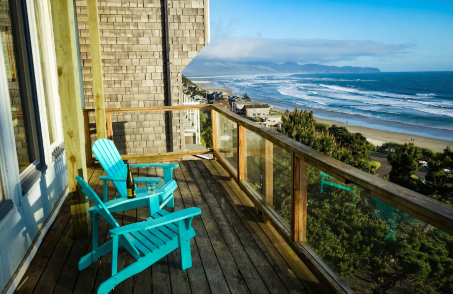 two blue chairs on wooden deck overlooking Pacific Ocean cabins in the USA