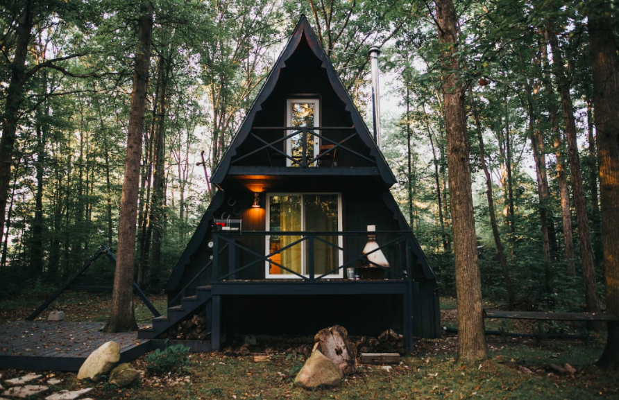two-story black A-frame cabin surrounded by trees cabins in the USA