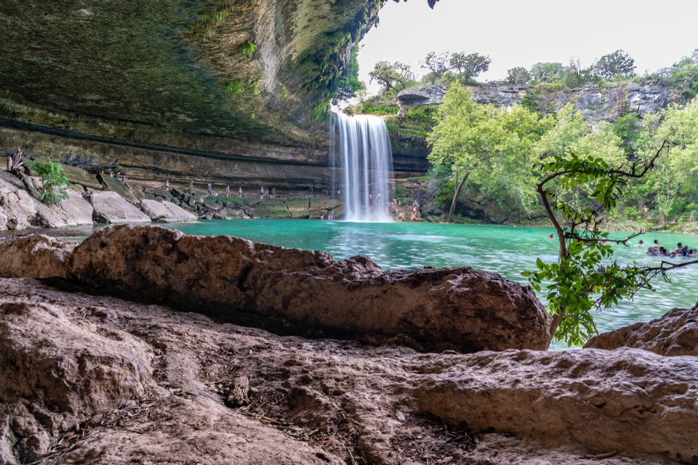 waterfall cascading into turquoise lake surrounded by pink rocks day trips from Austin