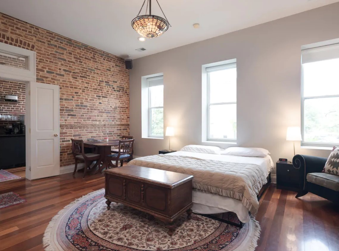 Bed along a wall of windows in a studio apartment in one of the best airbnbs of baltimore