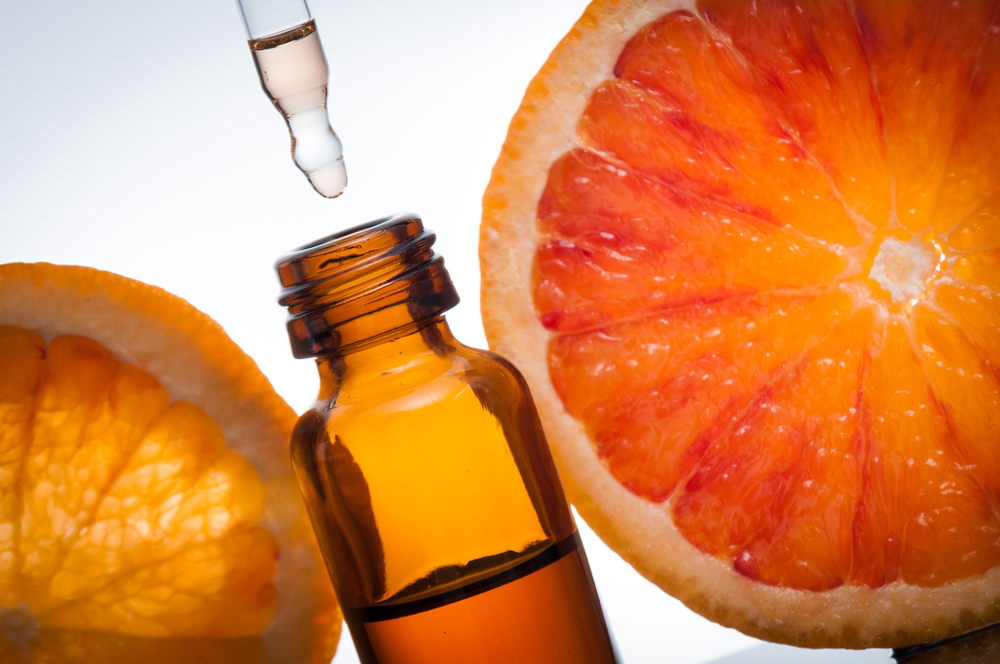 a picture of a oil bottle with oranges around it.