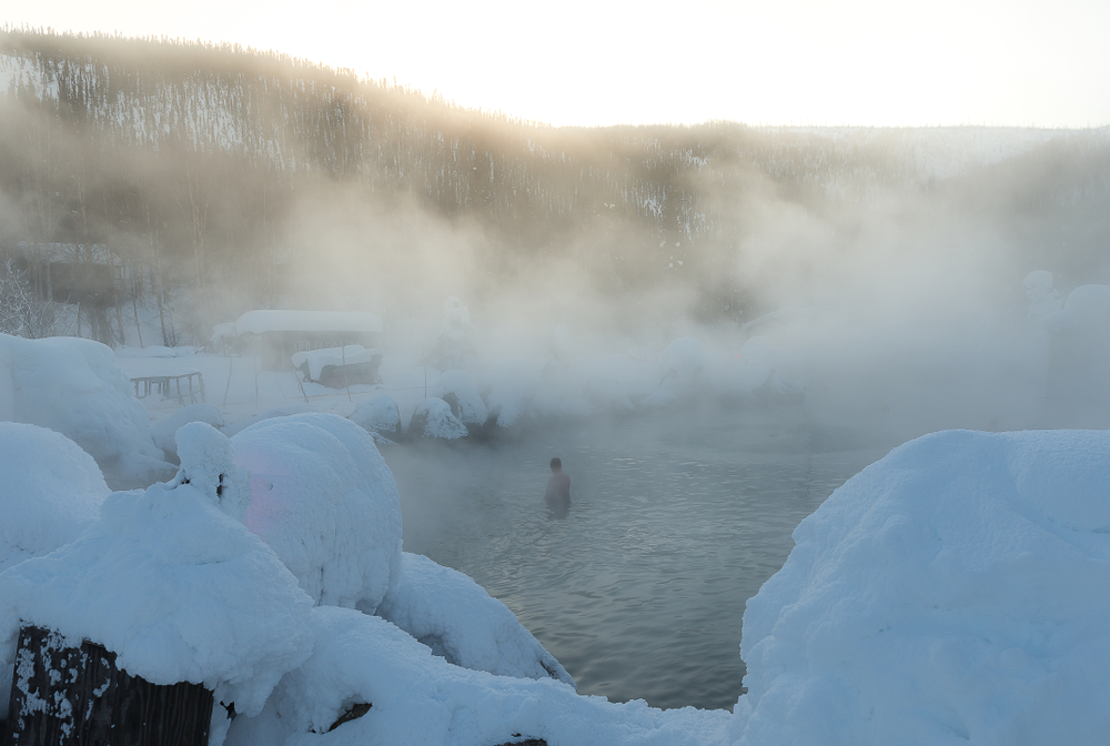 Smoke rises from the hot springs in the winter of Alaska.
