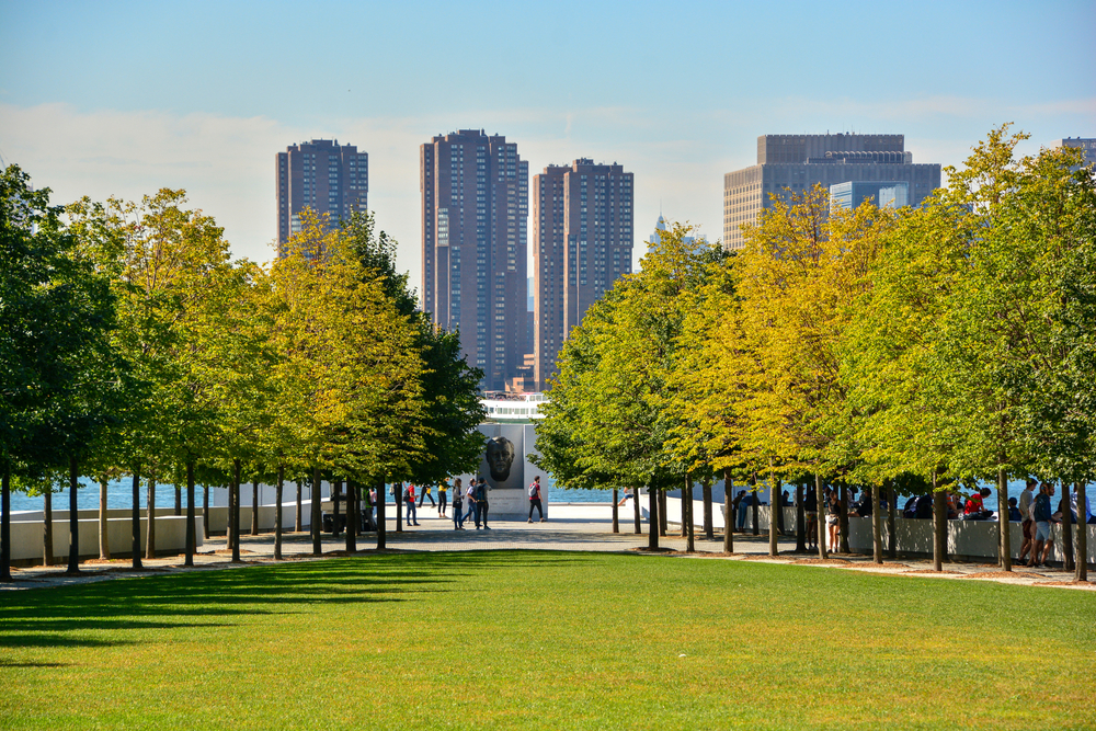 The view down Four Freedoms Park lane of trees with Manhattan in the background, one of the most unusual things to do in New York