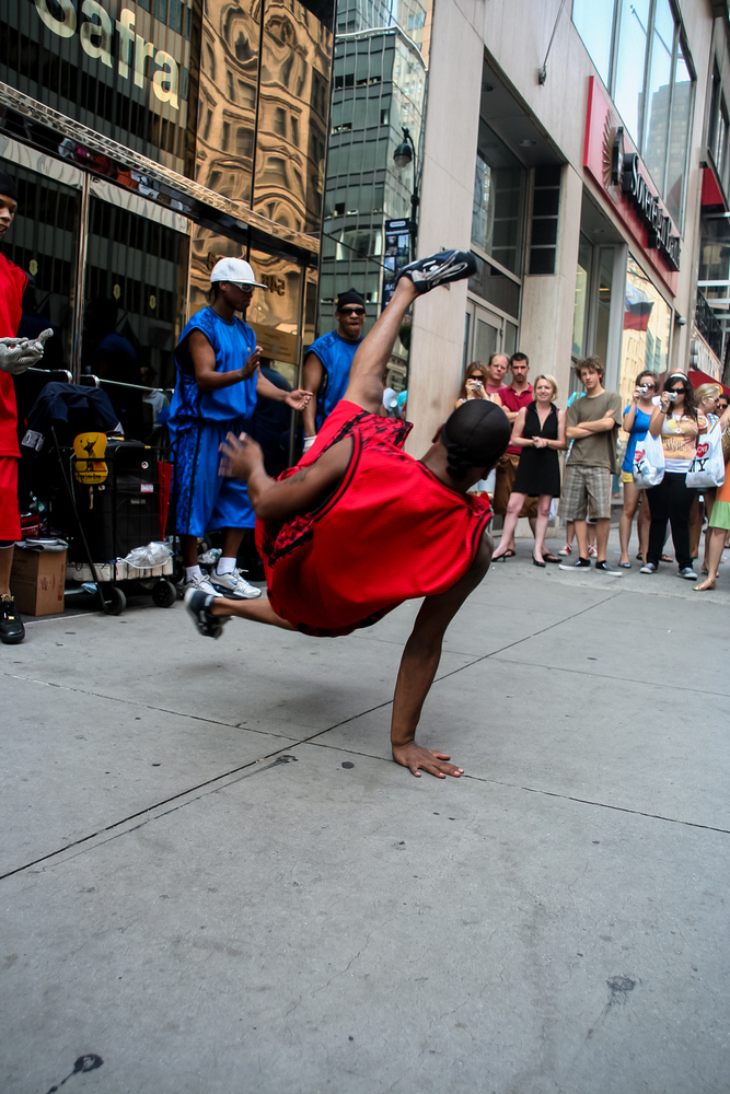 A person on the street break dancing surrounded by a crowd,
