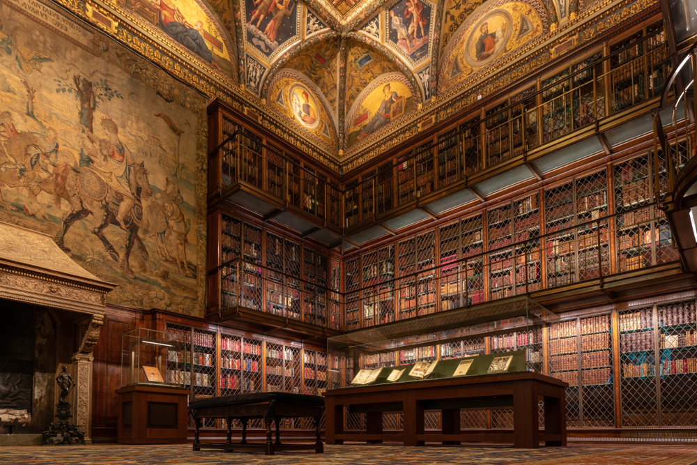 A room full of rare manuscripts with a large fireplace and tapestry at the Pierpont Morgan Library, one of the most unusual things to do in New York