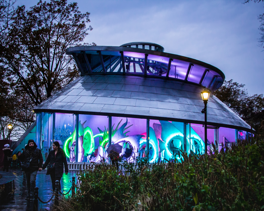 The outside of the SeaGlass Carousel lit up at night, one of the most unusual things to do in New York