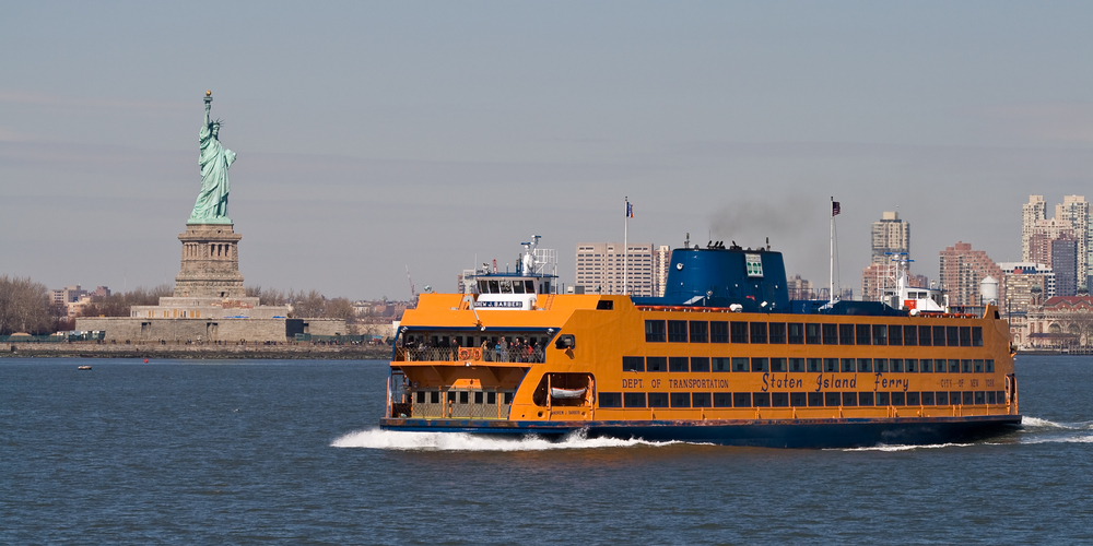 The Staten Island Ferry crossing the river with the Statue of Liberty in the background,