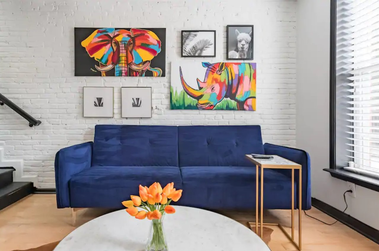 Dark blue sofa against a white brick wall with vibrant paintings on it one of the best airbnbs in baltimore
