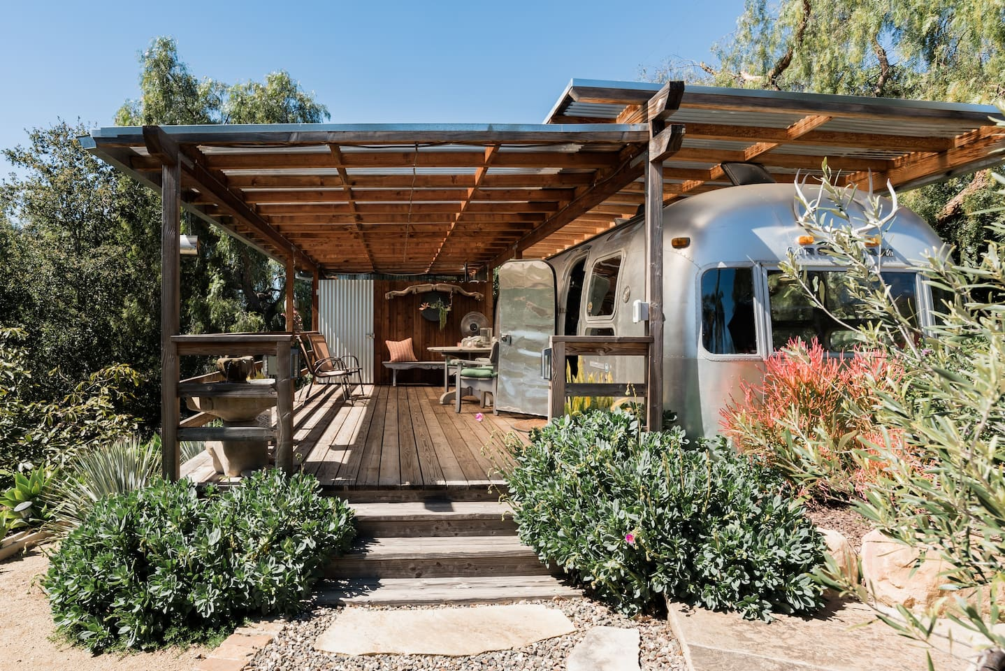 Cool Airbnb in California... 1974 Airstream, with a wooden deck and awning attached, surrounded by plants and trees.
