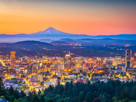 Portland city skyline at sunset with Mt. Hood visible in the distance.