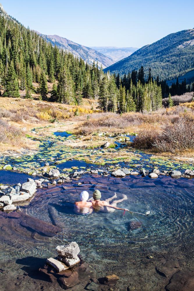 Photo of a couple enjoying mountain views from a hot springs in Colorado