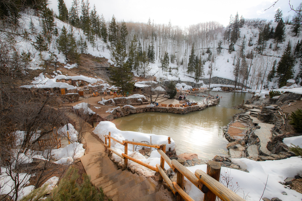 A photo of Strawberry Park Hot springs, a natural hot springs in Colorado, covered in snow.