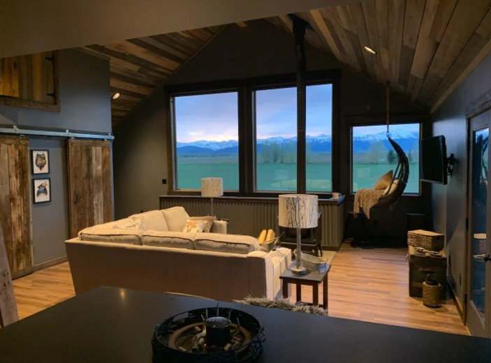 A view of a living room with picture windows overlooking the Teton mountains one of the best cabins in Idaho