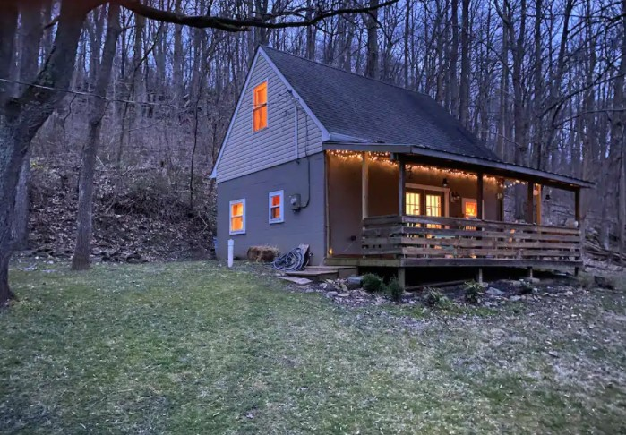 Exterior of a cozy cabin in Maryland with twinkle lights on the front porch during twilight