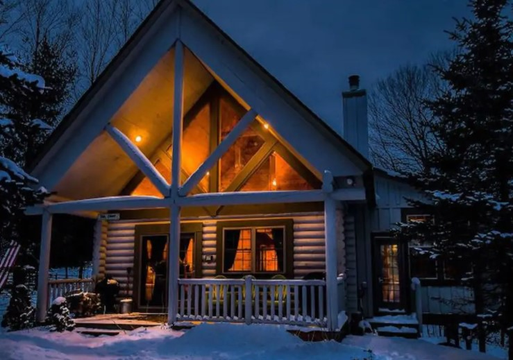 Outside view of cozy cabin in Maryland blanketed in snow with light glowing from the windows