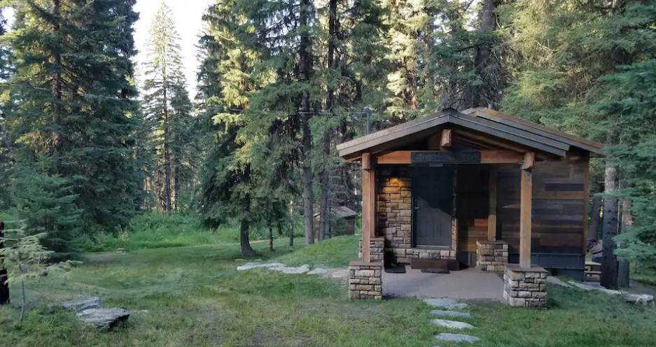 Wood and stone front cabin surrounded by tall trees and greenery one of the best cabins in Idaho