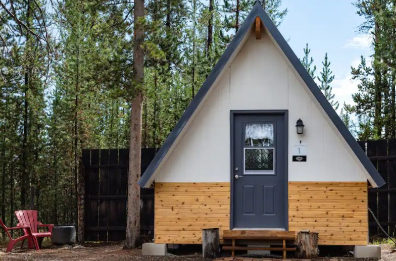 Front view of a simple A-frame cabin with a dark fence behind it and surrounded by trees