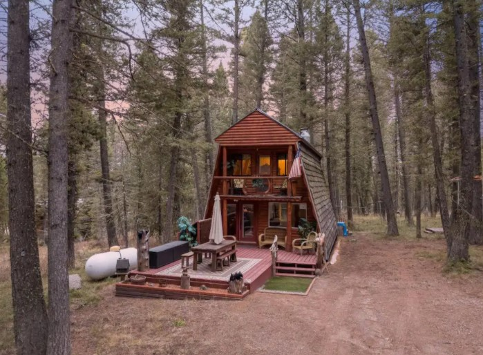 The front of a wide A-frame cabin with a two story porch surrounded by trees