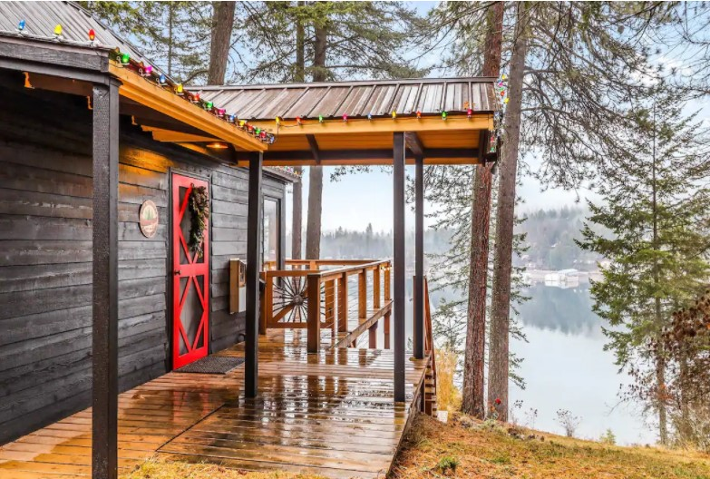 Side view of a front porch on a dark wood cabin with a red door with a view of a large lake behind it