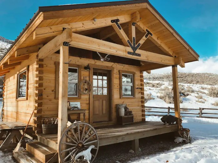 The front of a small cabin dusted with snow with hills in the background one of the best cabins in Idaho