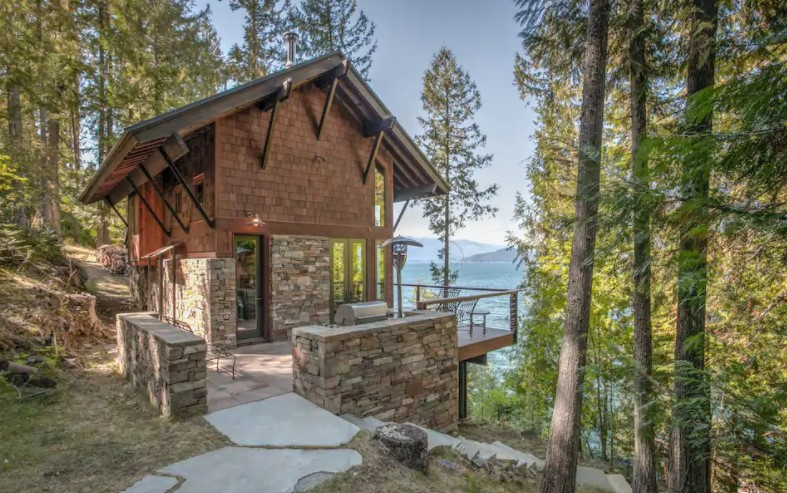 Side view of a luxury stone and wood shingle cabin with a front porch overlooking a large lake one of the best cabins in Idaho