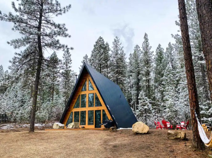 a frame cabin surrounded by tall pines dusted in snow one of the most cozy cabins in Idaho