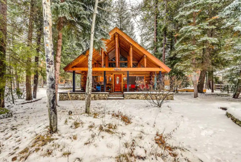 Front view of a traditional log cabin surrounded by tall pines with a light dusting of snow one of the best cabins in Idaho