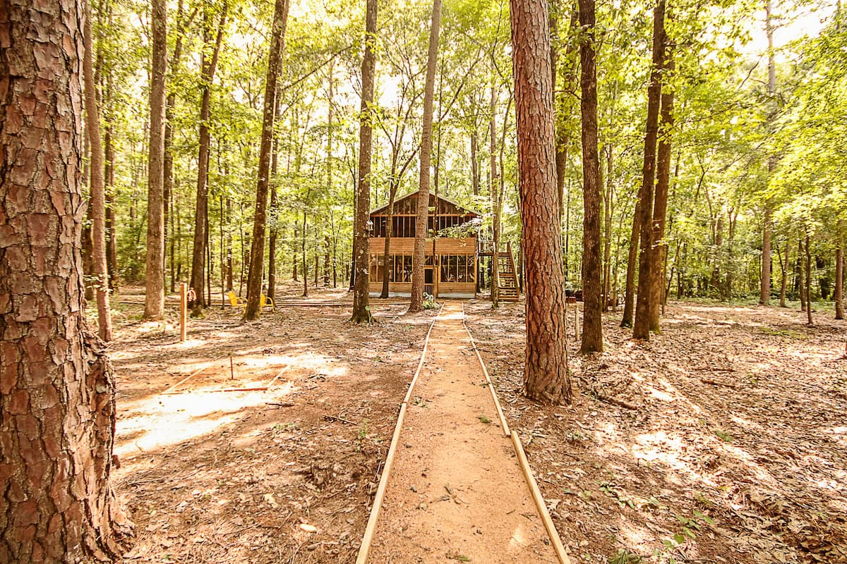 A Texas cabin among hundreds of beautiful trees, green and well lit.