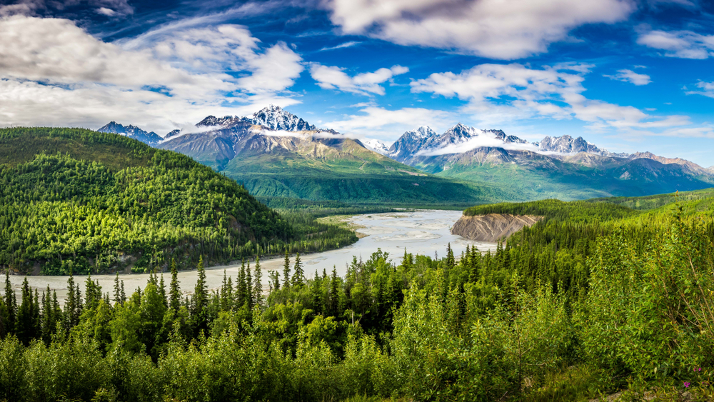 Alaska landscape with a large river surrounded by tall trees with mountains in the distance one of the best honeymoons in the usa