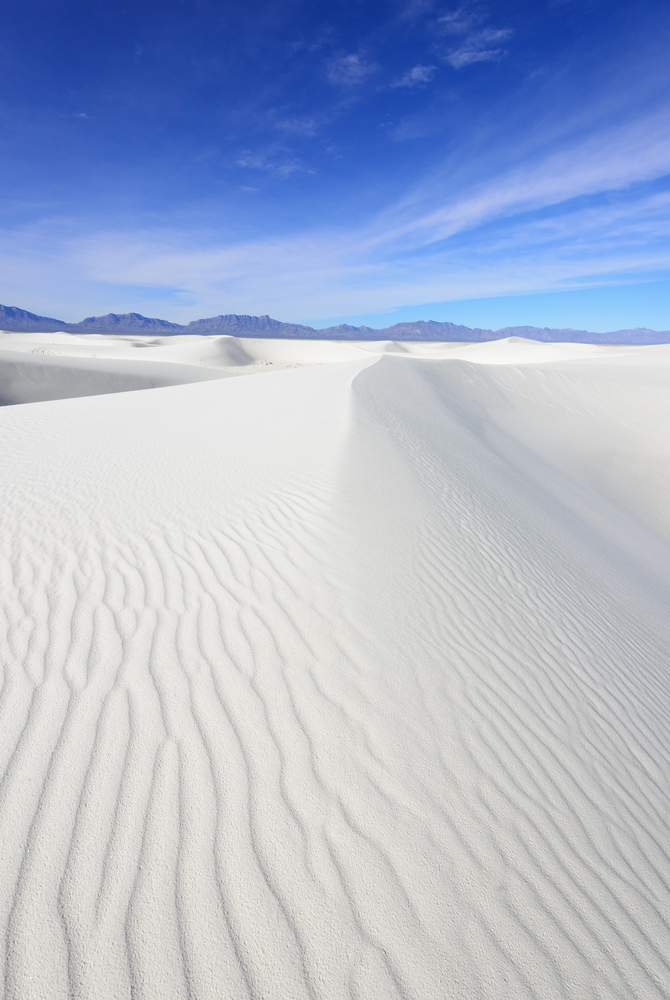 Untouched pure white sand stretches out for miles with mountain ranges on the horizon at the Alkali Flats Trail