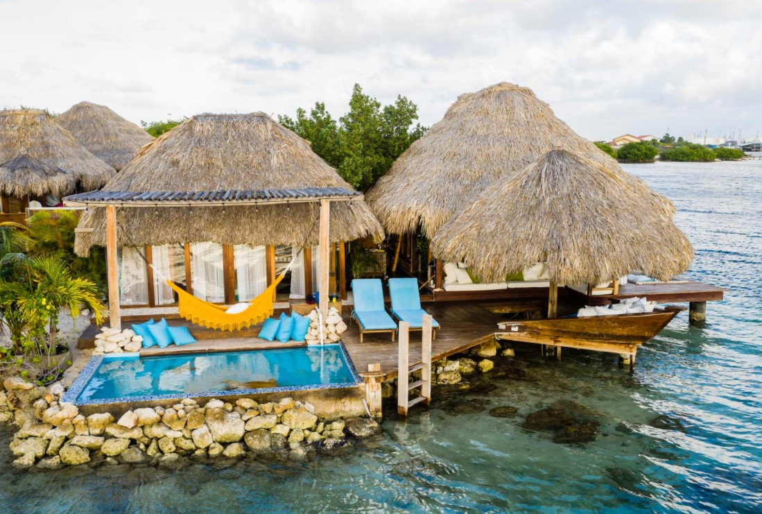 An arial view of a luxury overwater bungalow near the usa with its own private plunge pool, lounging area, and ocean views