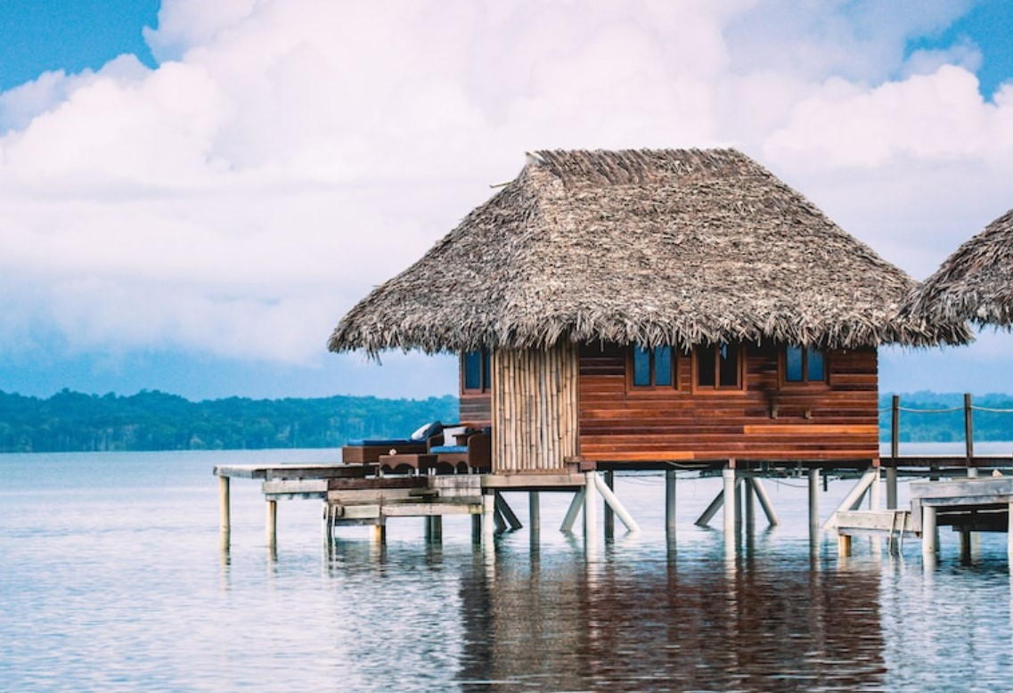 A thatched roof bungalow standing in beautiful water with its own private deck with hills in the far distance